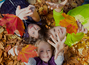 Kids laying in leafs