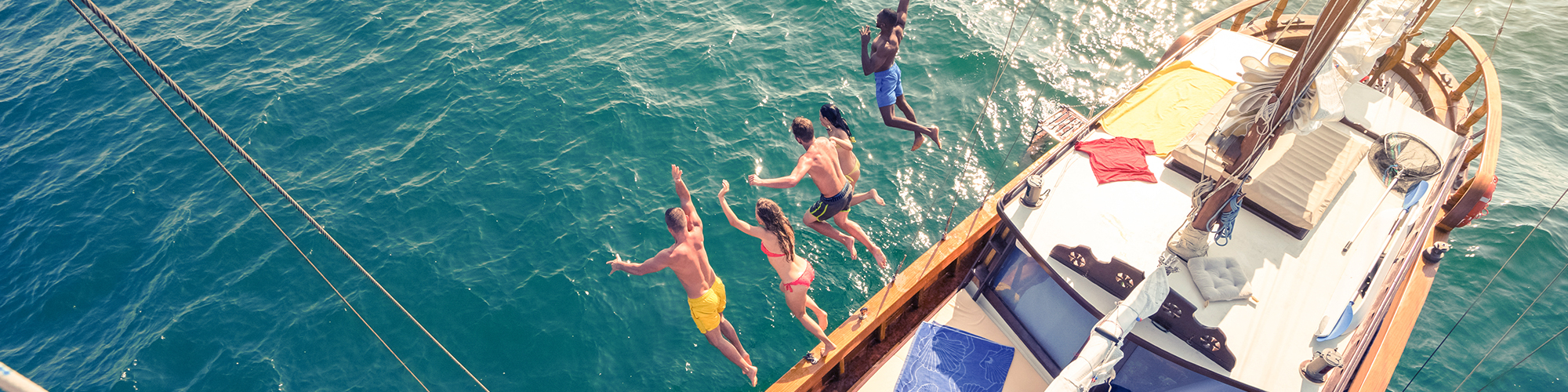 Friends jumping off a boat
